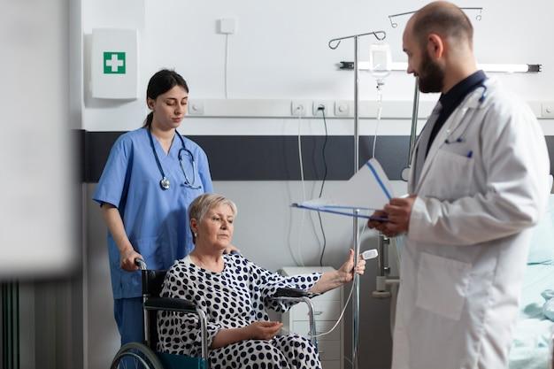 Paziente anziano malato seduto sulla sedia a rotelle dell'ospedale che riceve un trattamento