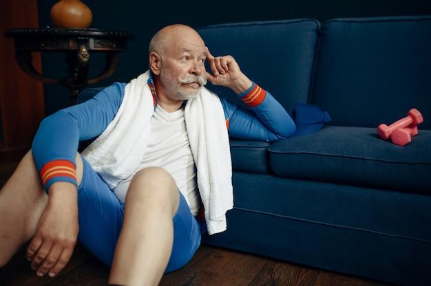 Sportivo anziano in uniforme rilassante dopo l'allenamento a casa. persona di sesso maschile adulto su allenamento fitness al chiuso, stile di vita sano nella vecchiaia