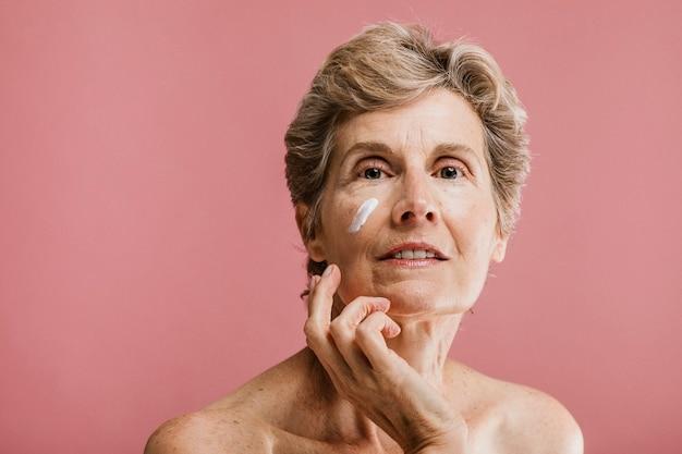 Donna anziana che applica la crema per il viso