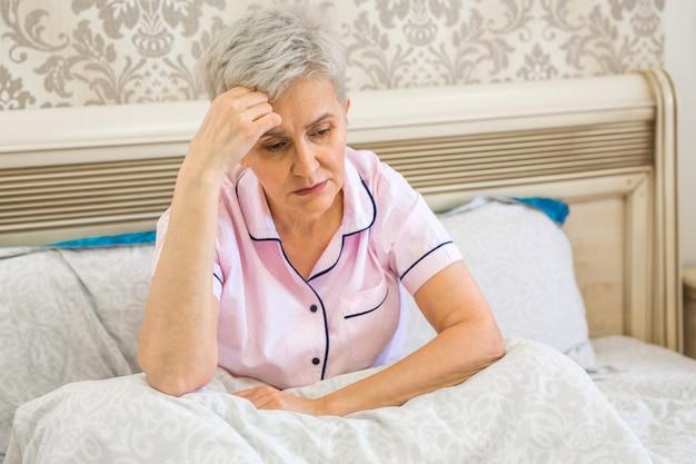 Donna anziana sul letto a letto sotto le coperte