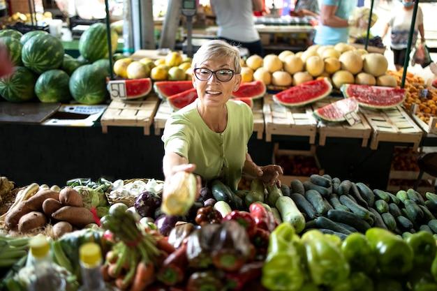 Donna anziana che acquista verdure biologiche fresche al mercato per un nutrimento sano.