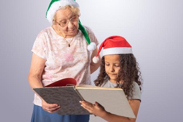 Donna anziana e bambino con il cappello di natale che legge un libro su gray