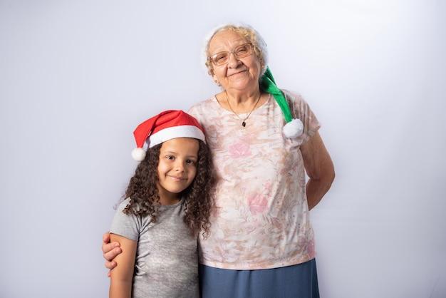Donna anziana e bambino con il cappello di natale insieme su gray