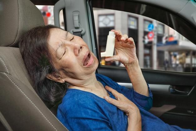 Donna anziana che soffoca e tiene in mano uno spray per l'asma all'interno dell'auto in arrivo