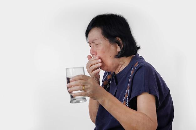 La donna anziana che soffoca una bevanda dell'acqua dopo prende la medicina, isolata su bianco