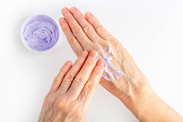 La donna anziana che scrematura le sue mani si chiude in su. cura cosmetica idratante per la vecchia pelle. cura e trattamento delle mani anti-età. unguento per il trattamento delle articolazioni per gli anziani.