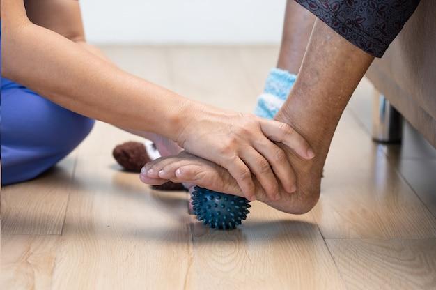 Donna anziana che fa palla di gomma per esercitare i muscoli delle dita, del palmo, della mano e del piede con il caregiver.