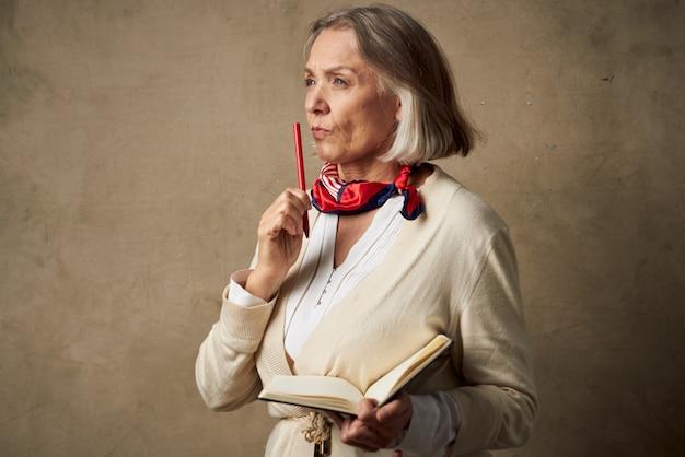 Donna anziana in vestaglia con un taccuino in mano studio