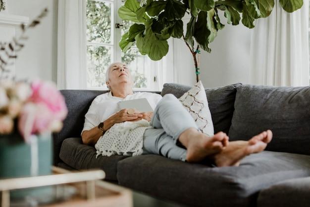 Una donna anziana si è addormentata su un divano con un tablet sul petto