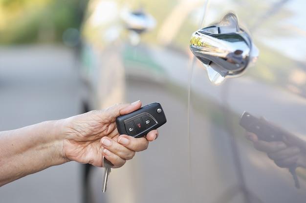 La mano della donna anziana apre l'auto sui sistemi di allarme chiave dell'auto
