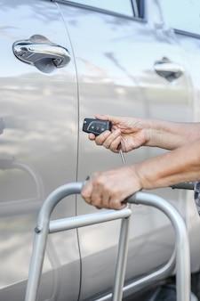 La mano della donna anziana apre la macchina sui sistemi di allarme per auto chiave