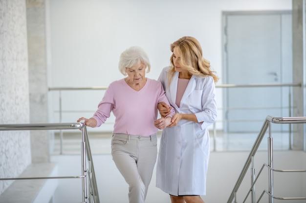Donna anziana e il suo medico che salgono le scale