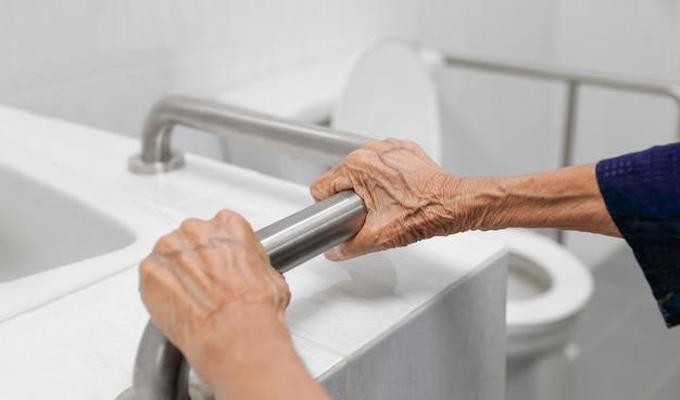 Donna anziana che tiene il corrimano in bagno