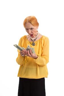 La donna anziana che tiene i soldi ha isolato la signora sorpresa che guarda i contanti conta le spese