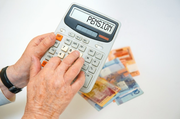 Una donna anziana tiene in mano una calcolatrice e calcola le spese. concetto finanziario