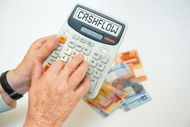 Una donna anziana tiene in mano una calcolatrice. iscrizione calcolatrice - flusso di cassa.
