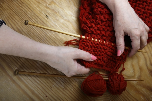 La donna anziana è impegnata a lavorare a maglia maglioni caldi per i suoi nipoti