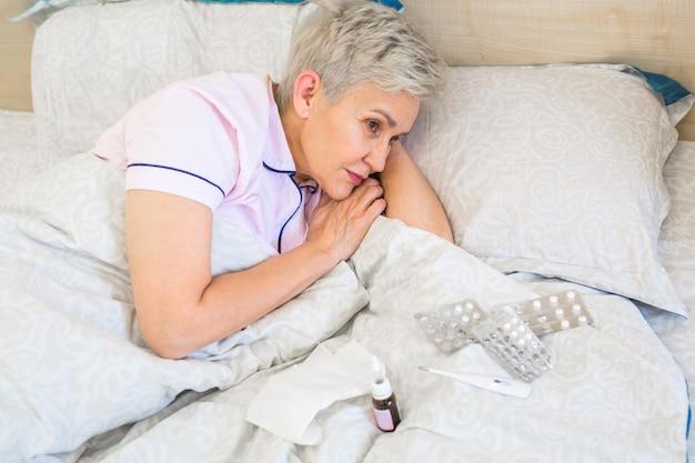 La donna anziana si trova su un letto con le pillole