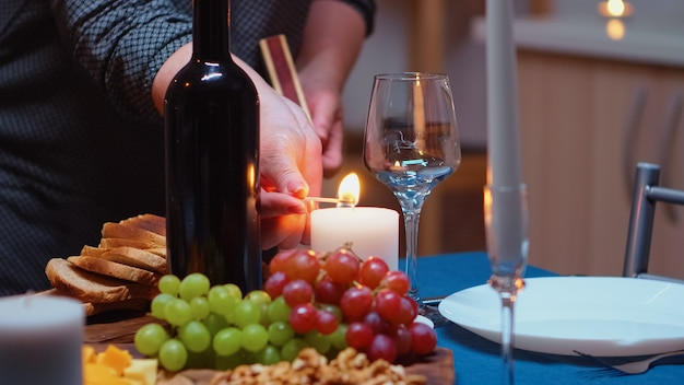 Donna anziana che accende la candela aspettando il marito per una cena romantica. anziana moglie anziana che prepara un pasto festivo con cibo salutare per la celebrazione dell'anniversario, seduta vicino al tavolo in cucina.
