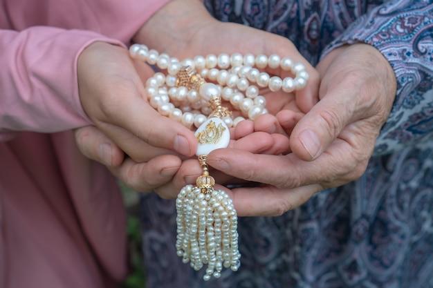 Una donna anziana e una bambina tengono in mano un bellissimo rosario bianco. mani di una donna anziana e di una bambina con il primo piano del rosario di perle. concetto religioso.