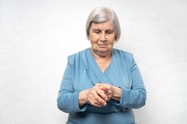 La donna anziana massaggia i palmi dolorosi