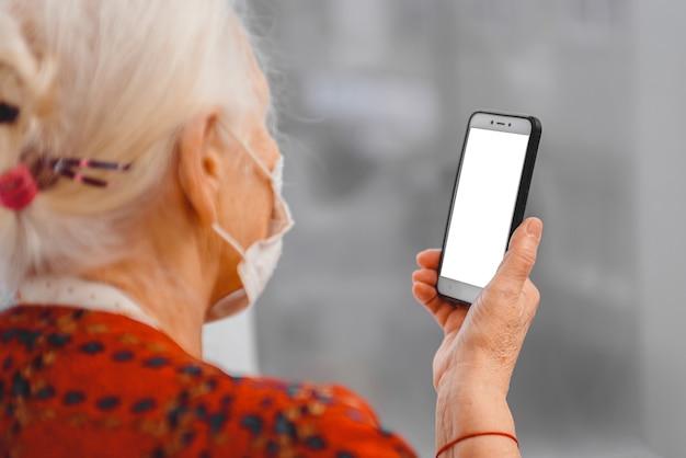 Una donna anziana in una mascherina protettiva medica guarda lo schermo dello smartphone