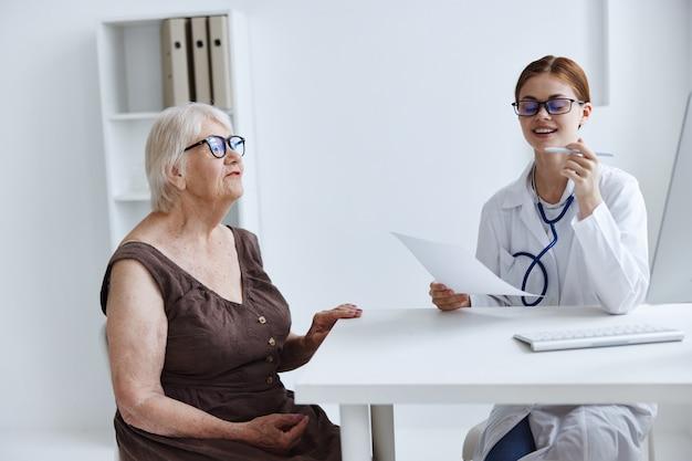 Esame del paziente della donna anziana da parte di uno stetoscopio medico