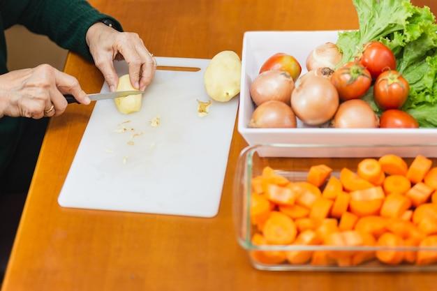 Donna anziana peeling potatoe con coltello nel tavolo della cucina.