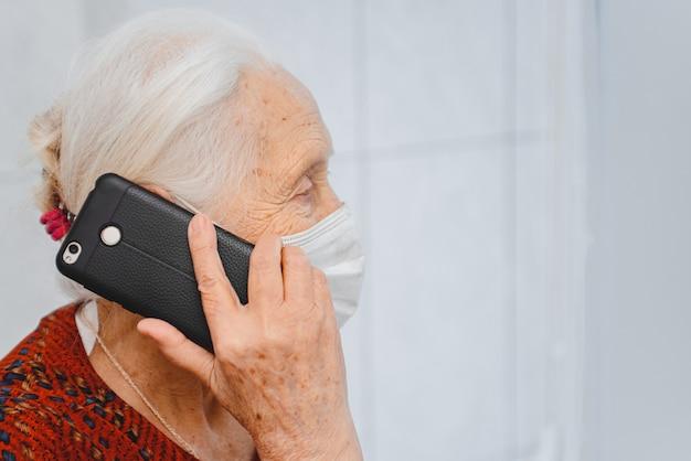 Donna anziana nella mascherina medica protettiva parlando su un telefono cellulare
