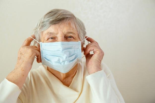 Una donna anziana si mette una mascherina medica sul viso. donna con mascherina medica preoccupata per il coronavirus