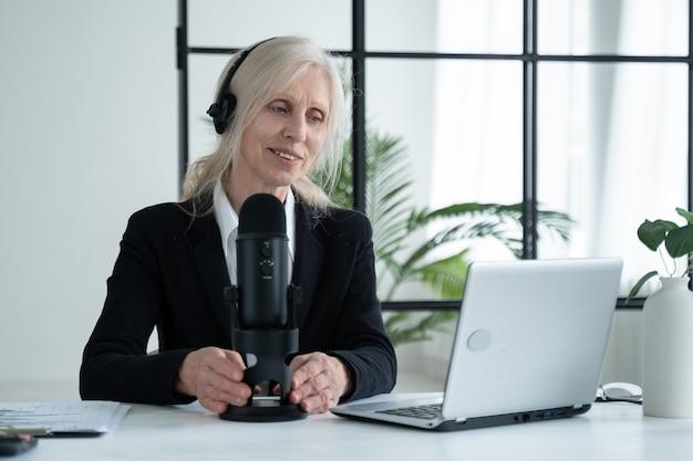 Una donna anziana registra un podcast sul suo laptop con cuffie e microfono
