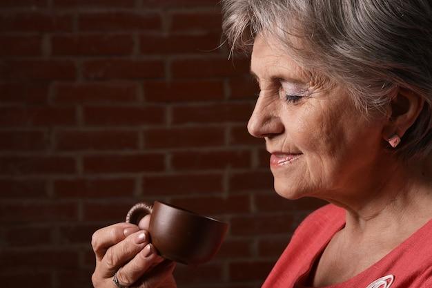 Donna anziana in rosso che beve caffè sullo sfondo di un mattone