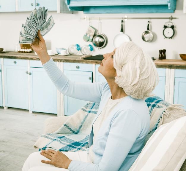 La donna anziana si rallegra tenendo in mano un fan di soldi