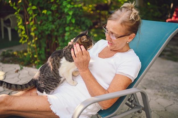 Donna anziana rilassante in giardino con un gatto