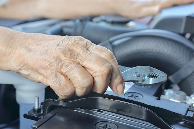 Donna anziana che ripara la sua auto