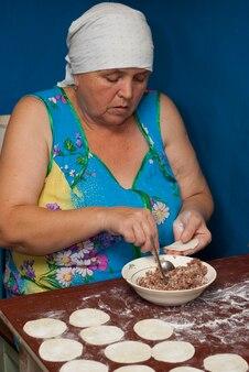 Donna anziana scolpisce pelmeni, vita rurale
