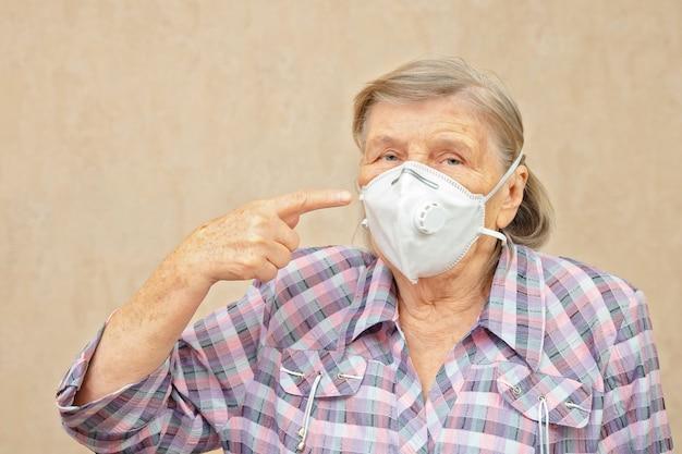 Una donna anziana mostra di indossare una maschera protettiva. la donna si preoccupa per il coronavirus