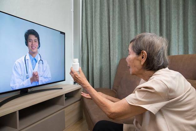 La donna anziana si siede a casa avendo consultazione online con il medico.