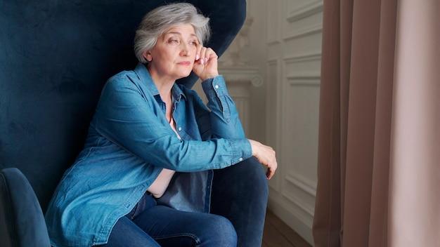 La donna anziana si siede da sola su una sedia a casa e guarda fuori dalla finestra. un pensionato sta riposando in soggiorno.