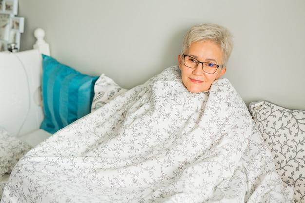 La donna anziana si siede su un letto in una coperta