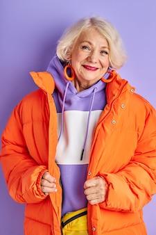 Donna anziana in cappotto sportivo guarda la fotocamera e sorride, in posa, preparata per il clima invernale