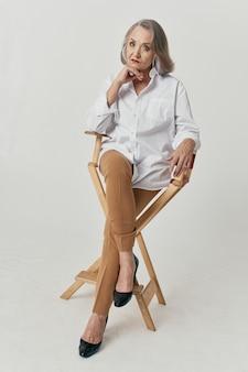 La donna anziana sta vicino ad una posa della camicia bianca di stile di vita della sedia