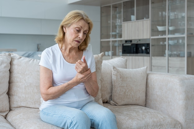 Una donna anziana che soffre di artrite delle mani seduta sul divano il concetto di mentale