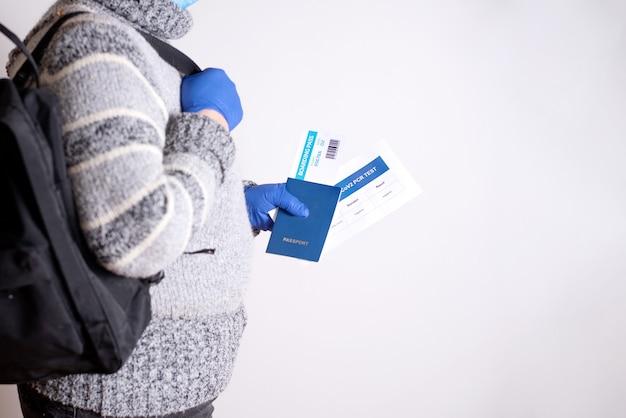 Una donna anziana con un maglione e uno zaino con in mano i documenti per il viaggio aereo: passaporto, biglietto, test pcr covid-19 su uno sfondo bianco, spazio di copia.