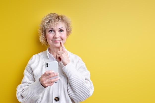 Donna anziana che pensa mentre si chatta con qualcuno al telefono, tenendo lo smartphone moderno nelle mani, compongono un'idea, toccando il mento
