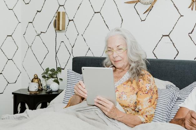 Donna anziana che usa un tablet a letto