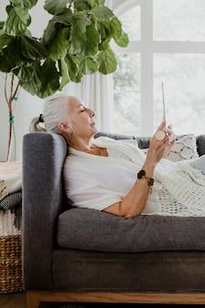 Donna anziana che usa un tablet su un divano
