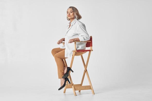 Donna anziana in camicia bianca che si siede su uno stile di vita del primo piano della sedia