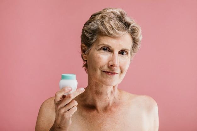 Donna anziana con un mockup di contenitore di crema