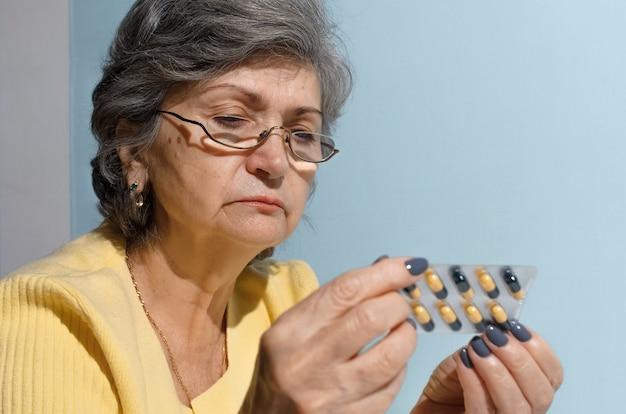 Donna anziana con gli occhiali, cercando di leggere le istruzioni delle pillole medicinali, close-up. concetto di trattamento, pensionamento per malattia
